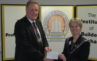 The Master presenting a cheque to Rebecca Mason Past President of the Institute of Builders Merchants